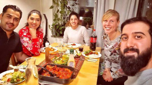 Fem personer sitter runt ett bord som är uppdukat med maträtter, såser och drickor