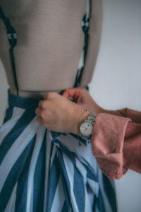 En persons händer som arbetar med en blåvitrandig klänning som sitter på en provdocka.