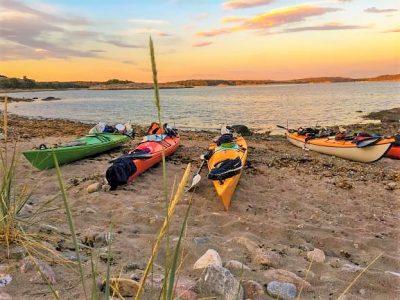 fyra kajaker som ligger på en strand. I bakgrunden syns vattnet och en solnedgång.