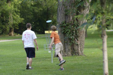 Två unga personer kastar en frisbee mot en korg
