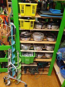 En grön hylla med saker som lånas ut på Fritidsbanken som till exempel stormkök, isborrar och termosar.