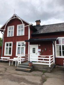 Ett rött gammalt stationshus hus med vita fönster där Hållplats loppis har sin verksamhet.