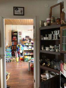 Två rum fyllda med loppisprylar som porslin och barnsaker.