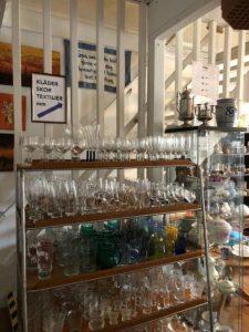 En hylla med glas i olika färger. I bakgrunden syns ännu en hylla med glas och porslin.