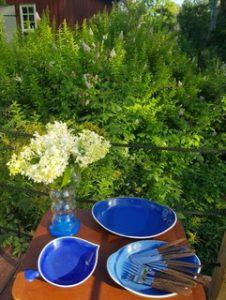En servis i blått står på ett träbord. På en tallrik ligger bestick. En vas med vita stora blommor står också på bordet. I bakgrunden en grön buske.