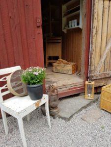 En röd bod med öppen dörr. Utanför står en vit stol med en blomma i rosa på. Äldre ljuslyktor står vid båda sidorna av dörren.