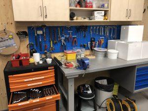 Arbetsbänk, på väggen bakom hänger diverse verktyg.