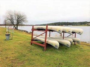 Ställning med kanoter som ligger upp och ned, i bakgrunden syns vattnet.