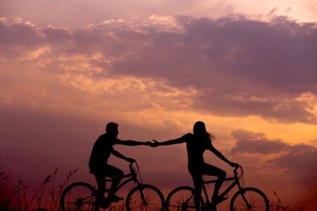 Två personer som cyklar i solnedgång, de håller varandra i handen som för att dra varandra framåt