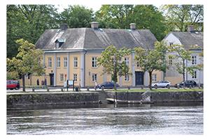 Klarälven, på andra sidan ett äldre gult hus med gråa knutar.