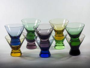 Glas med en mindre fot. Glasen är i färgerna blå, grön, gul och lila.