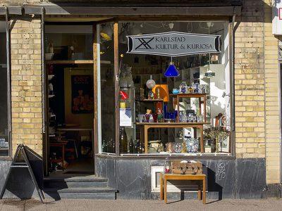 kultur och kuriosas skyltfönster fyllt med porslin- och glasartiklar. Till exempel glas, vaser och lampor.
