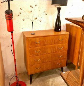 En teakbyrå med en svart lampa på och en spretig retrodekoration. Till vänster om byrån står en röd lampa.