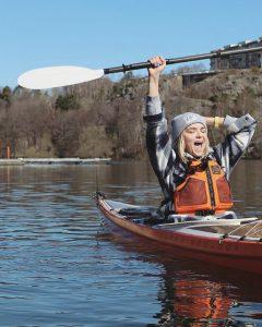 Glad kvinna i en kajak som lyfter paddeln över huvudet