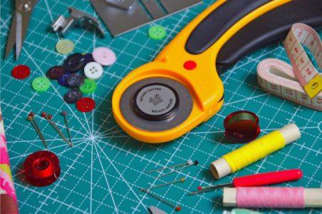 Tygskärare, måttband, knappnålar, sytrådsrullar, sax och knappar ligger på ett sybord