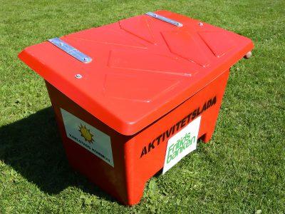 Röd stor låda med texten Aktivitetslåda tryckt på framsidan. På lådan finns även Fritidsbankens logga och Karlstads energis logga.
