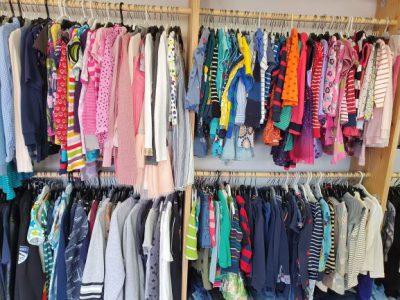 Massa barnkläder i alla möjliga färger som hänger på galgar i en butik.