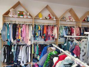Massa barnkläder i alla möjliga färger som hänger på galgar i en butik. Längst upp i bilden finns även några leksaker och mjukisdjur i trekantiga hyllor.