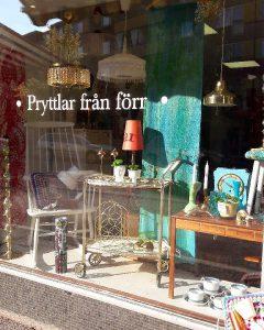"""Skyltfönster med texten """"pryttlar från förr"""". Retro möbler syns i skyltfönstret. En retro stol, drinkvagn, lampa, avlastningsbänk, taklapmor, gardin och porslin."""