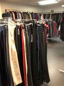Klädställning full med byxor i olika färger och modeller. I bakgrunden finns klädhängare med jackor, blusar och skjortor i olika färger.
