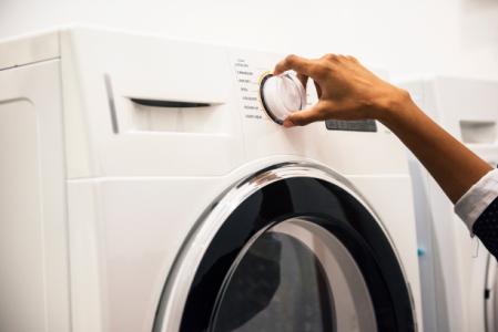 En hand som skruvar på ratten på en tvättmaskin.