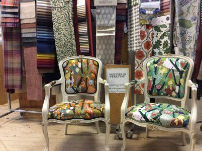 Två stolar som är tapetserade med ett mönstrat tyg. I bakgrunden finns tygprover i många olika färger och mönster.