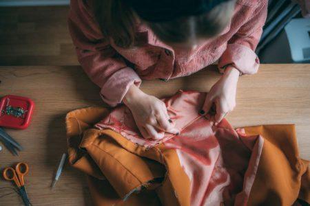 En skräddare som sitter och nålar ett klädesplagg som hon arbetar med.