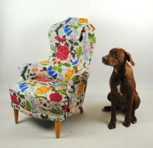 En fåtölj i blommigt tyg, bredvid en brun hund.
