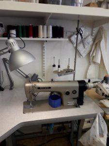 Ett arbetsbord med en grå symaskin. Trådrullar i olika färger i bakgrunden.