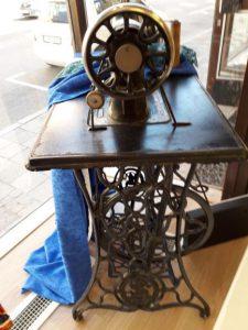 Äldre symaskin som sitter fast i sitt bord. Ett blått tygstycke hänger över ena kanten.