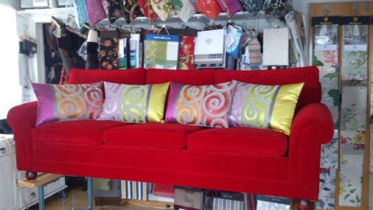 Röd soffa med kuddar i, gardintyger i bakgrunden.