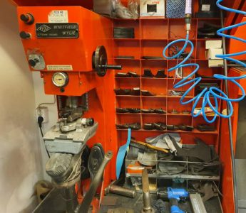 Röd maskin som är till för att laga skor. En svart känga sitter i maskinen för att lagas.