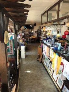 En översiktsbild inifrån butiken med tavlor, porslin och prydnadssaker.