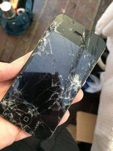 En svart mobiltelefon med trasig skärm.
