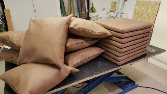 Beiga kuddar och sittdynor som ligger på ett bord.