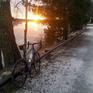 Svart landsvägscykel, lutad mot ett räcke vid en väg längs med vattnet. Solljus i fjärran