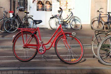 En röd damcykel stående utomhus och andra cyklar i bakgrunden.