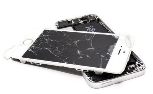 Vit mobiltelefon med trasig och avplockad skärm.