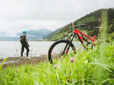 En strand med en röd mountainbike cykel och cyklisten på. Berg i bakgrunden.