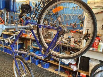 En cykel som servas. I bakgrunden finns hyllor och en vägg med verktyg.