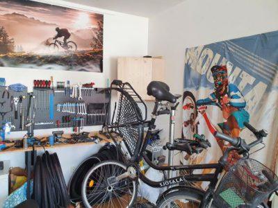 En svart damcykel som repareras på en cykelverkstad. I bakgrunden hänger massa olika verktyg och på väggarna affischer med proffscyklister.