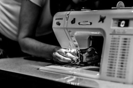 En person som trär på tråd i en symaskin.