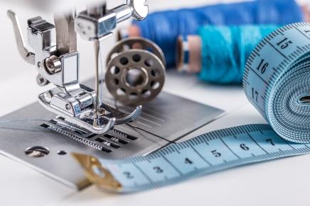 Symaskinsnålen, blått måttband, spole, trådrullar med olika nyanser av blått.