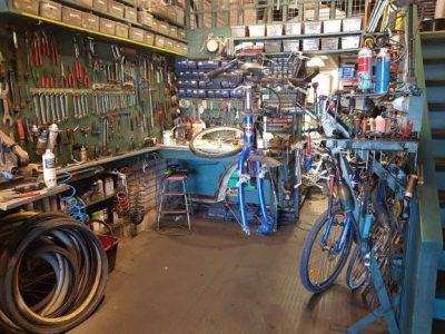 Cykelverkstad med verktyg och tillbehör. En cykel på lagning på en bänk.