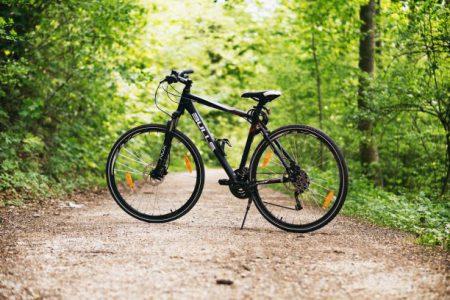 Svart cykel på en grusväg med skog omkring.