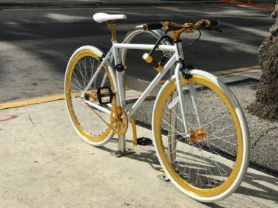 En herrcykel som står lutad mot ett cykelställ.