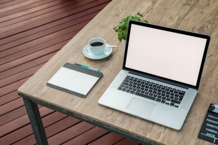 En dator på ett bord. Bredvid står en kaffekopp med kaffe i och en växt. På bordet ligger också en surfplatta.
