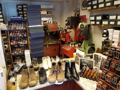 Flera par skor som står uppställda på en bänk. Samt mobilfodral och skärp i olika färger. I bakgrunden syns skomakarens verktyg och maskiner.