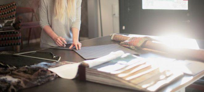 En person som mäter tyg på ett bord med tygprover.