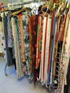 En klädställning med tyger och gardiner i blandade färger och mönster.